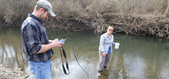 Two students test water samples at a local creek